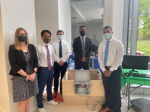 A team of students standing next to their completed prototype